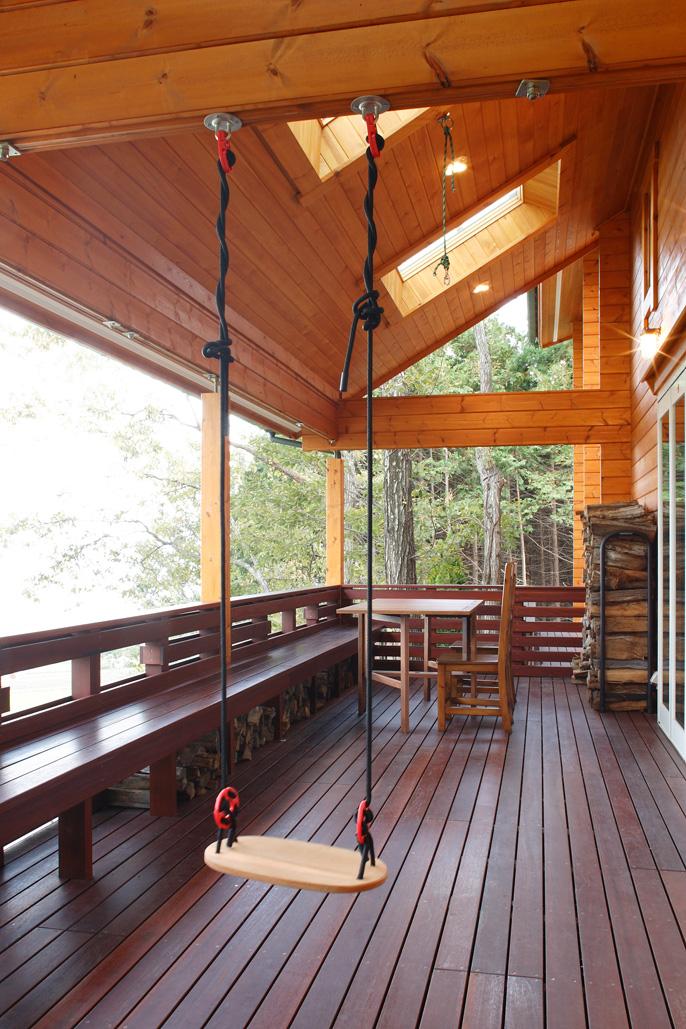 大人数でも使えるようにベンチを造り付けした インデッキ。雨の日でもオープンエアな 雰囲気のなかでパーティが楽しめる空間だ。 デッキには雨に強いウリン材を使用