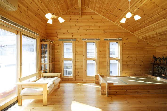 3つ並んだ縦長の大きな窓から光が差し込む 2階の寝室。ログ材で枠を組んで作った 特製ベッドもある